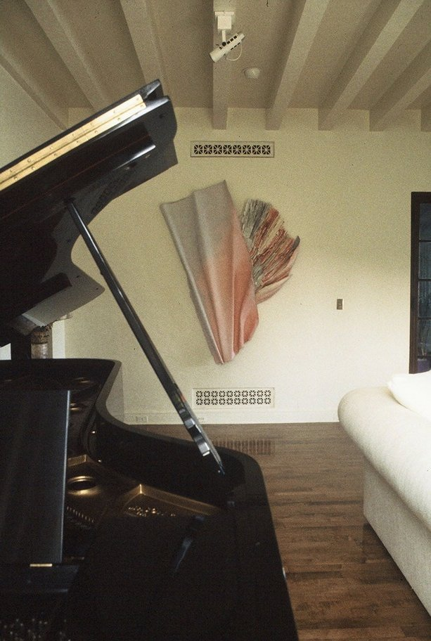 A large paper sculpture framed by a piano cover